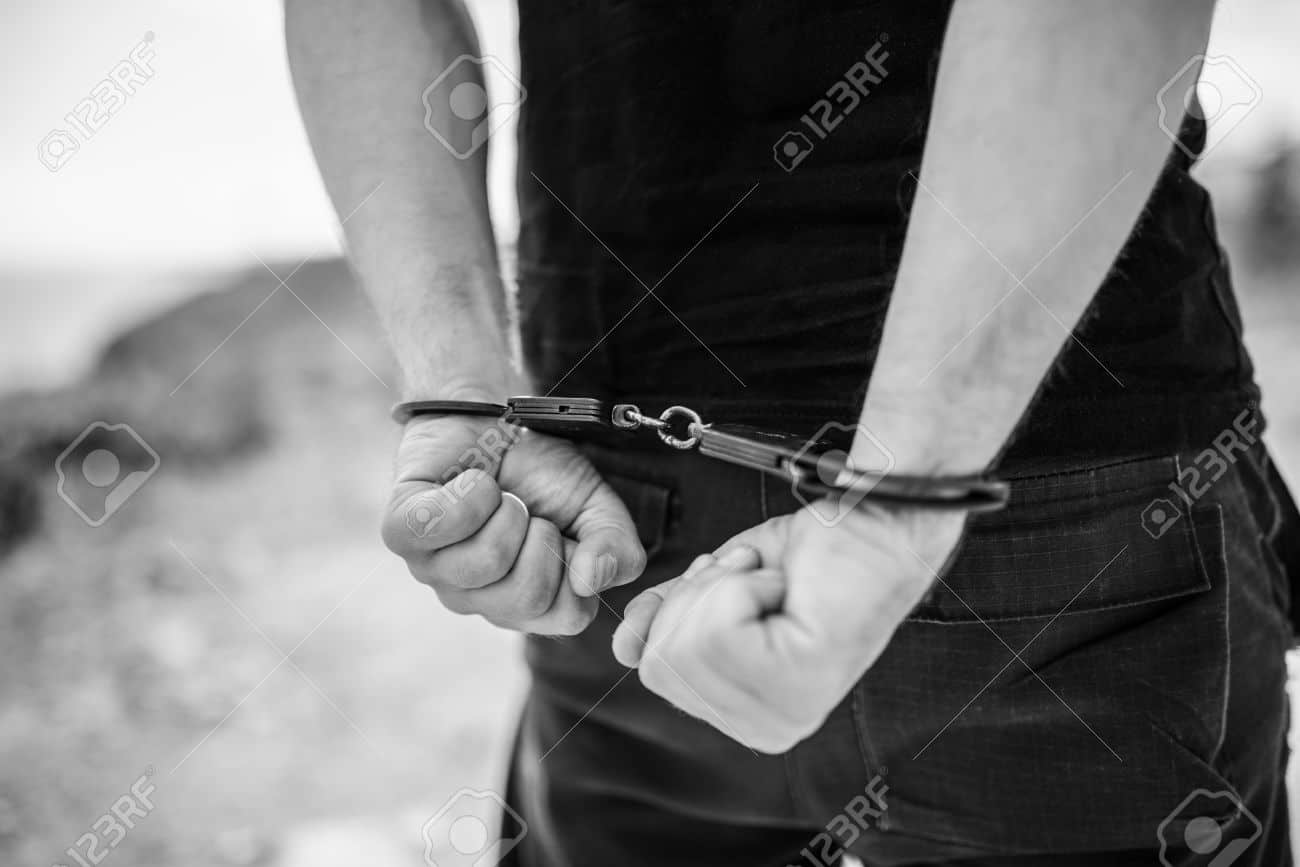 52351945-A-mens-hands-in-handcuffs-behind-his-back-Selective-focus-with-shallow-depth-of-field-Black-and-whit-Stock-Photo