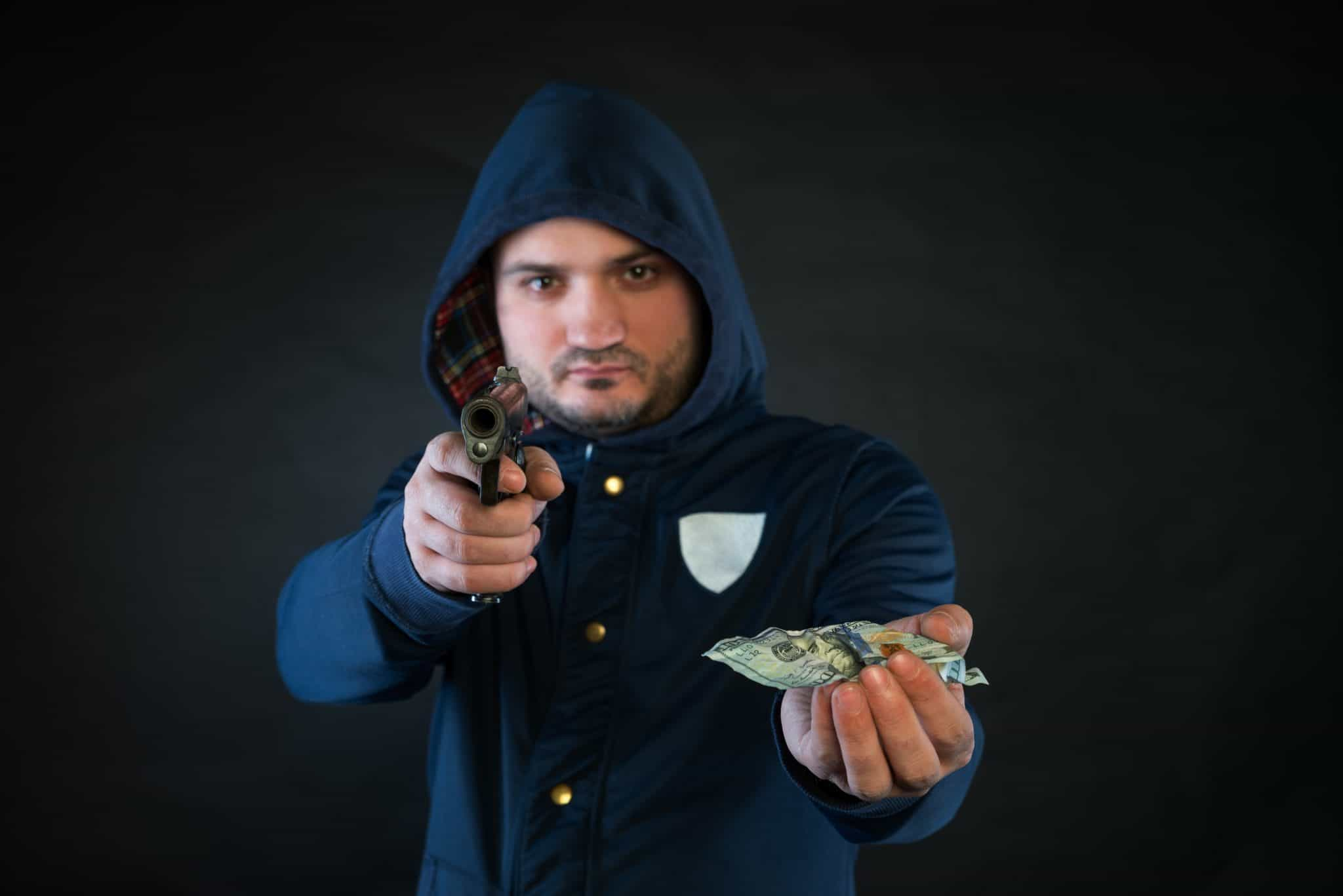 A person in a hoodie is aiming and holding the other hand with the dollar note