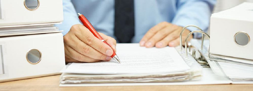 47720487 - midsection of businessman working  with financial documents at desk